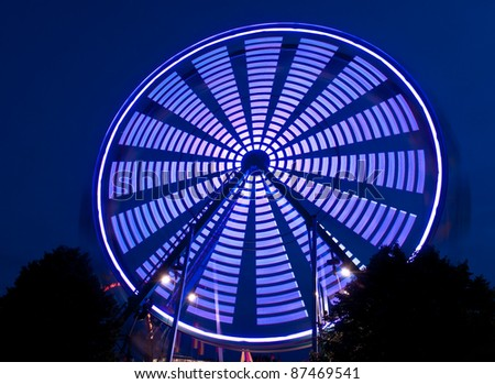 Blue Spinning Ferris Wheel - patterns created by lights on wheel - stock photo