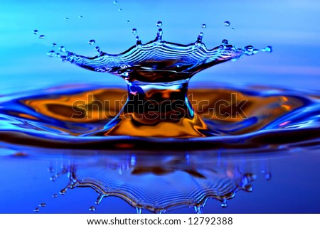 Blue splash in blue and orange colored water - stock photo