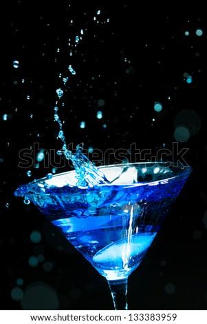 blue splashing cocktail on black - stock photo