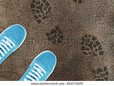 Blue sport shoe on street and shoes print around. - stock photo