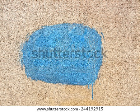 Blue spot of paint on stucco wall