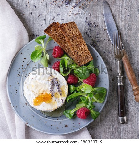 Blue spotted plate with fresh goat cheese, served with honey, honeycomb, lavender, raspberries, green salad and wholegrain toast on white textile over white wooden table. Flat lay. Square image - stock photo