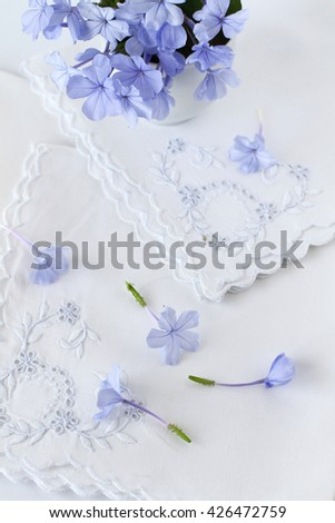 Blue Spring flowers on vintage embroidered linen  - stock photo