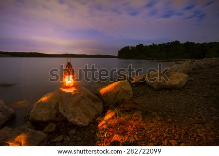 Blue Springs Lake located outside of Kansas City, Missouri at night with a lantern glowing light onto the rocky shoreline - stock photo