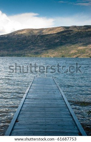 Blue stained wooden pier on Okanagan lake against the foothills of the Okanagan in British Columbia, Canada - stock photo