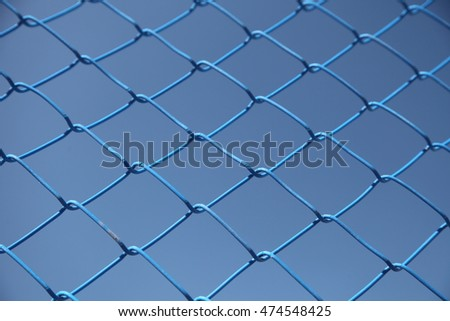Blue steel wire mesh fence. Blue sky background. Blue on blue