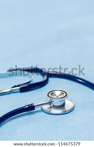 Blue stethoscope on medical cloth doctor's equipment close-up - stock photo