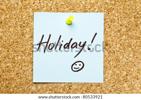 Blue sticky note on an office cork bulletin board with Holiday! on it. - stock photo