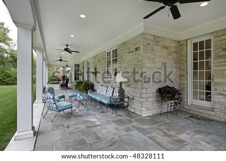 Blue stone patio with columns and blue furniture - stock photo
