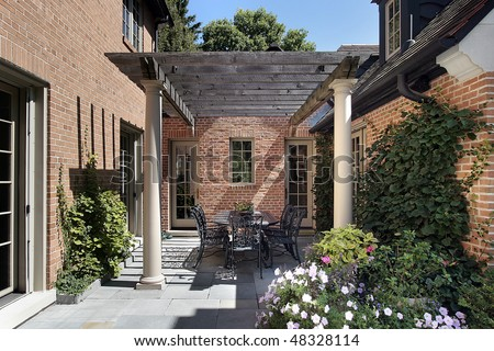 Blue stone patio with columns and wood pergola - stock photo