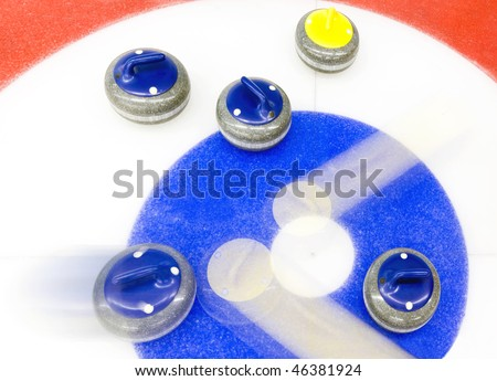 Blue stone precisely delivered, to bounce away two yellow stones from the house of a curling rink - the winning shot. - stock photo