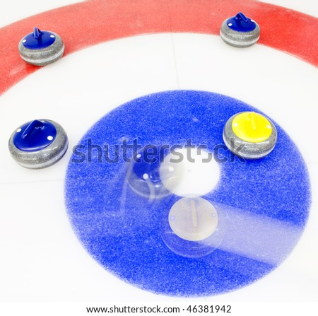 Blue stone taking the house by tapping away a yellow stone at a curling game - stock photo