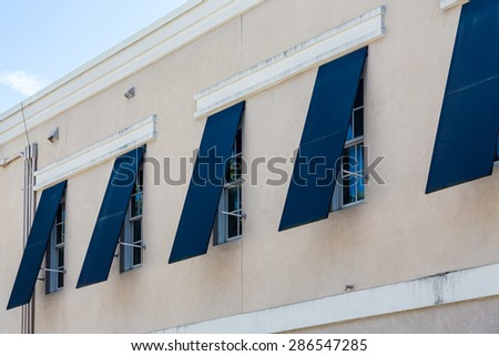 Blue storm shutters open on a new stucco building - stock photo