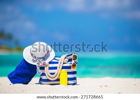 Blue stripe bag and towel, straw white hat, sunglasses, sunscreen bottle on exotic beach - stock photo