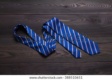 Blue striped necktie on black wooden table - stock photo