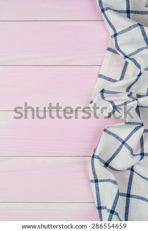 Blue striped towel over the surface of a wooden table. - stock photo