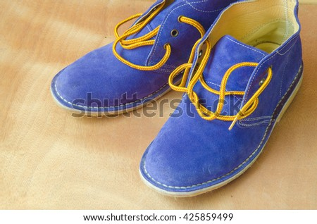 Blue suede shoes A shoestring yellow A suede classic style luxury accommodation on the wooden floor - stock photo