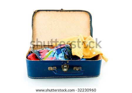 Blue suitcase with clothes on white background