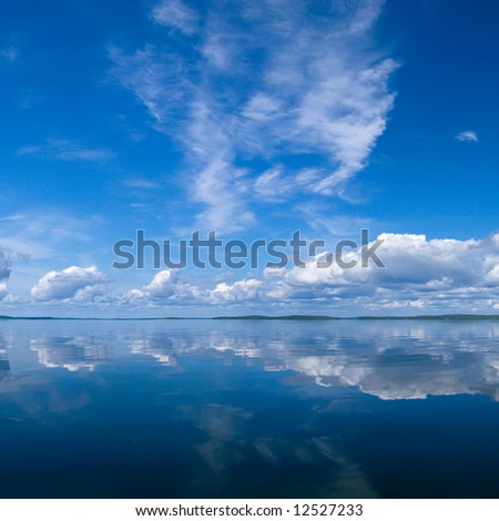 Blue summer bright sky reflecting in lake - stock photo