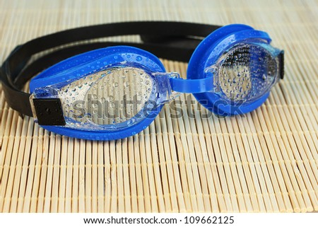 blue swim goggles with drops on a bamboo pad
