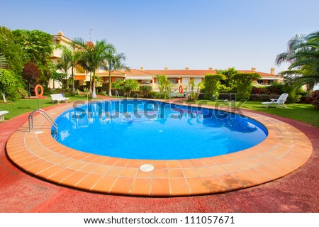 blue swimming pool in exotic tropical garden