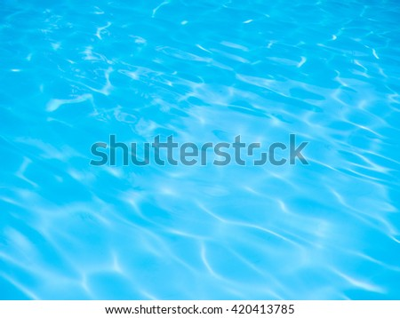 Blue swimming pool rippled water detail background with sunny reflections - stock photo
