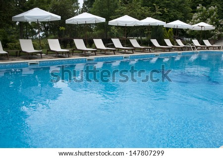 Blue swimming pool , sunbeds and umberalla for sunbath in bulgaria