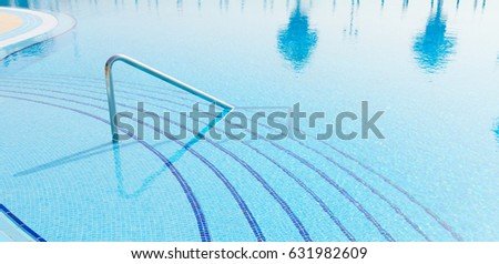 blue swimming pool with  reflections of palm trees