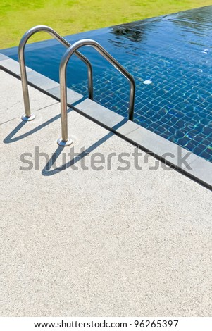 Blue swimming pool with sand washed flooring summer vacation - stock photo