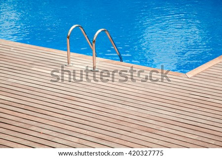 Blue swimming pool with teak wood floor stripes summer vacation