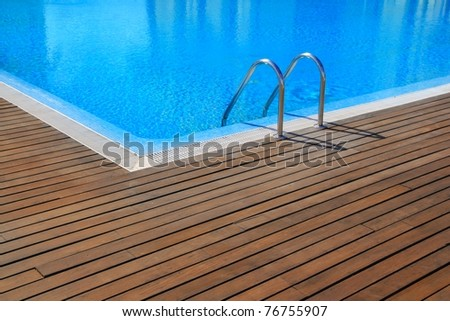 blue swimming pool with teak wood flooring stripes summer vacation - stock photo