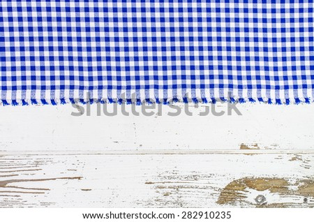 Blue tablecloth over wooden table - stock photo
