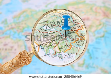 Blue tack on map Asia with magnifying glass looking in on Phnum Penh, Cambodia, Asia - stock photo