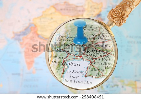 Blue tack on map of Asia with magnifying glass looking in Bangkok, Thailand - stock photo