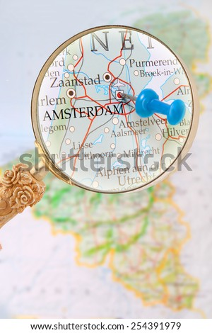 Blue tack on map of Benelux with magnifying glass looking in on Amsterdam, Holland - stock photo