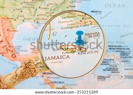 Blue tack on map of Caribbean with magnifying glass looking in on Kingston, Jamaica  - stock photo