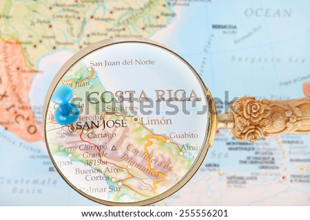 Blue tack on map of Central America with magnifying glass looking in on San Jose, Costa Rica - stock photo