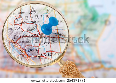 Blue tack on map of central Canada with magnifying glass looking in on Edmonton, Alberta - stock photo