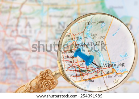 Blue tack on map of central Canada with magnifying glass looking in on Winnipeg, Manitoba - stock photo
