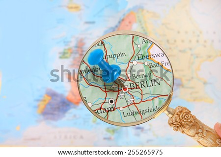 Blue tack on map of Europe with magnifying glass looking in on Berlin, Germany - stock photo