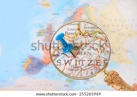 Blue tack on map of Europe with magnifying glass looking in on Bern, Switzerland - stock photo