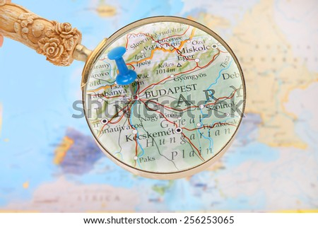 Blue tack on map of Europe with magnifying glass looking in on Budapest, Hungary - stock photo
