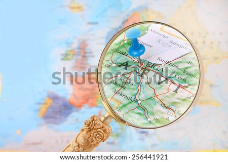 Blue tack on map of Europe with magnifying glass looking in on Riga, Latvia - stock photo