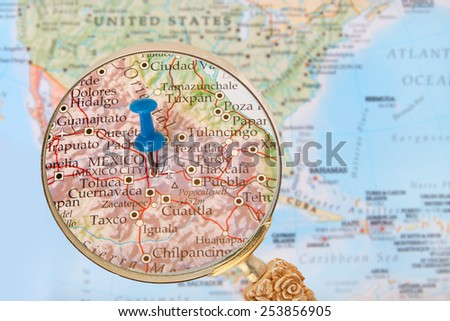 Blue tack on map of North America with magnifying glass looking in on Mexico City the capitol of Mexico - stock photo