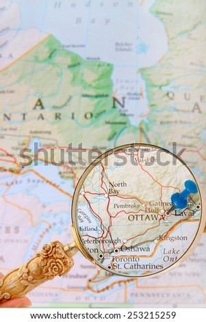 Blue tack on map of Ontario with magnifying glass looking in on Canada's capital city, Ottawa, Ontario - stock photo