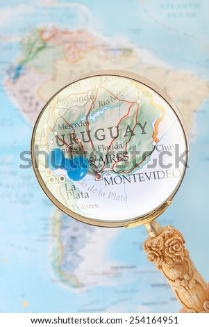 Blue tack on map of South America with magnifying glass looking in on Montevideo the capitol of Uruguay - stock photo