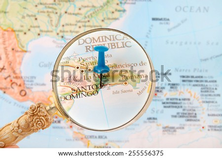 Blue tack on map of the Caribbean with magnifying glass looking in on Santo Domingo, Dominican Republic