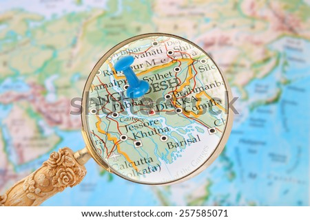 Blue tack on map of the world with magnifying glass looking in on Dhaka, Bangladesh - stock photo