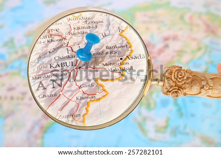 Blue tack on map of the world with magnifying glass looking in on Kabul, Afghanistan, Asia - stock photo