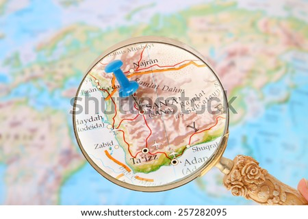 Blue tack on map of  the world with magnifying glass looking in on Sana, Yemen, Asia - stock photo